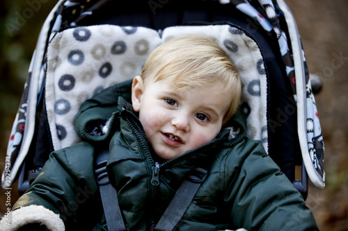Portrait of a young boy sitting in a stroller, smiling