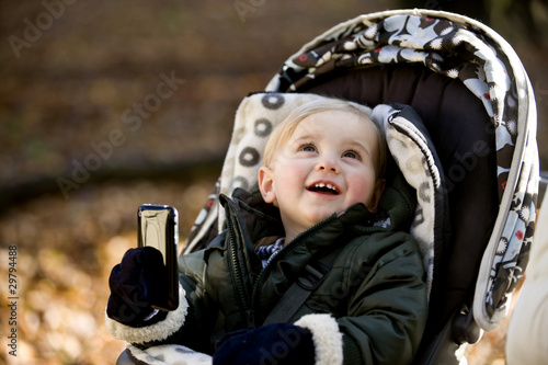 A young boy in a stroller holding an iphone, smiling