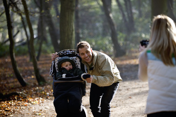 A mother photographing her partner and child in the park