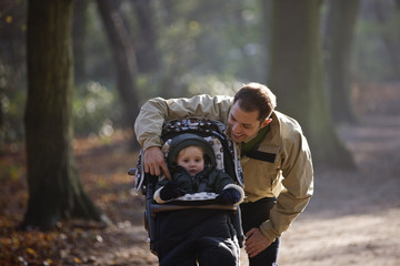 A young father with his son in a stroller in the park