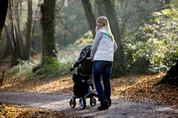 A young mother pushing a stroller in the park, smiling