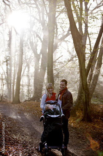 A young couple pushing a stroller in the park, talking