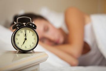 Young sleeping woman in bedroom.
