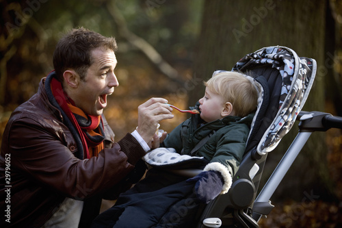 A young father feeding his son in the park