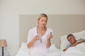 Woman taking pills at home