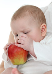 Little baby trying to eat an apple