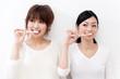two beautiful asian women blushing her teeth