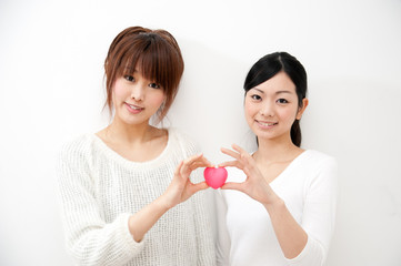 two beautiful asian women holding a symbol of heart