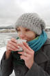 The young white frozen girl drinks hot tea in the winter