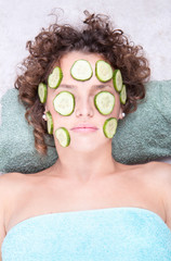 Woman relaxing under a cucumber face masque