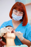 Image of young lady with dentist over her checking oral cavity . poster