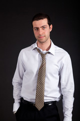Serious young businessman isolated on black