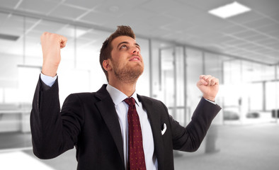 Energetic businessman with arms raised.