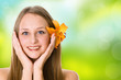 Beautiful woman face with a flower on green blurred background