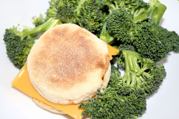 English muffin with cheese slice and broccoli