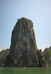 Ha Long Bay, Vietnam- Touristboat infront of high cliff.