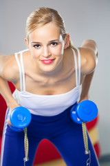 Woman exercising with dumbbells and expander at home