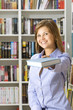 Young woman stretches the book in the library