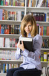 Young woman with big book in the library