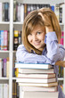 Young smilling woman sitting with books in the library