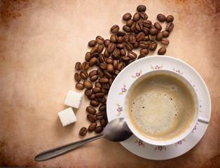 cup of freshly brewed black coffee. top view. focus on beans