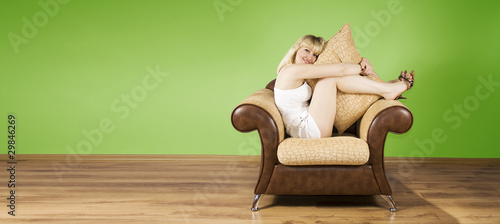 Cheerful young woman sits in an armchair