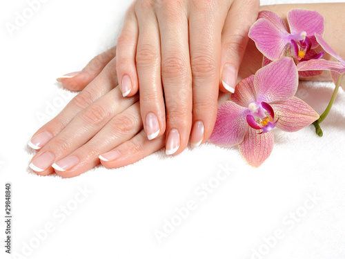 Beautiful hand with perfect nail french manicure and purple orch