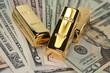 drei Goldbarren auf Dollarscheinen