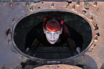 Mujer subiendo por las escaleras de una trampilla