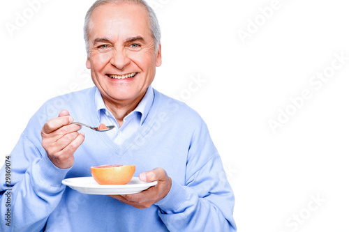 Happy mature man eating a grapefruit
