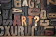 The word 'Art?' spelled out in very old letterpress blocks.