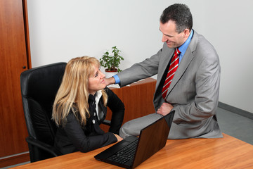 Businessman and businesswoman flirting in the office