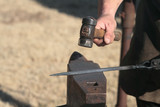 blacksmith hammering iron bar on anvil poster