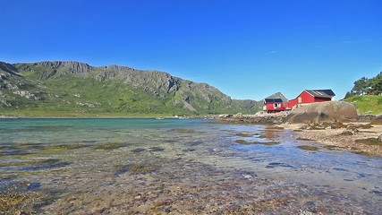 Red wooden house near quiet waters