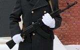 White gloves hands of a honor guard holding a Kalashnikov poster