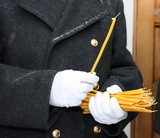 White gloves hands of a honor guard holding a candle bunch poster