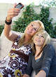 Mother and Teenage Daughter Taking Pictures with Mobile Phone Ca