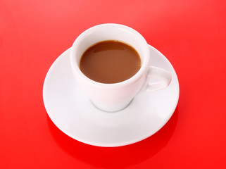 Small white cup with coffee on red background