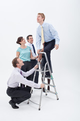 Businesspeople helping businessman climbing up ladder