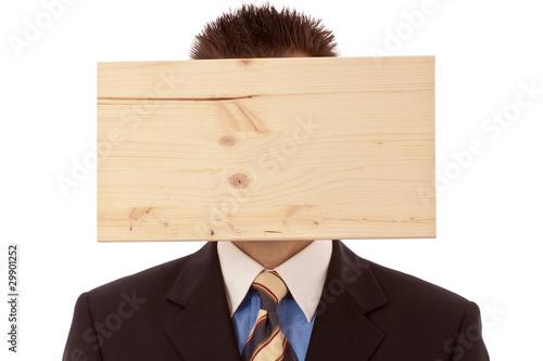 Mann-Geschäftsmann mit Denkblockade-Brett vorm Kopf