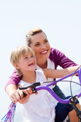 pretty mom and daughter riding bike