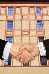 Businessmen shaking hands in front of the Modern Building