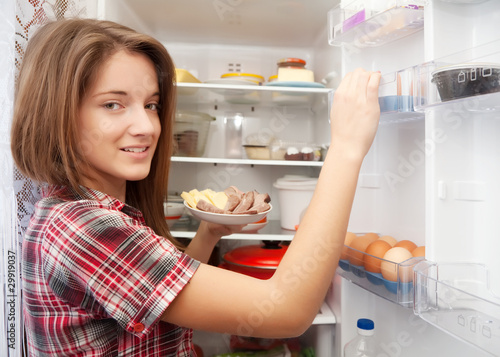 girl putting snack into refrigerato