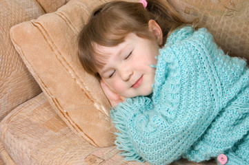 The little girl sleeps on a sofa