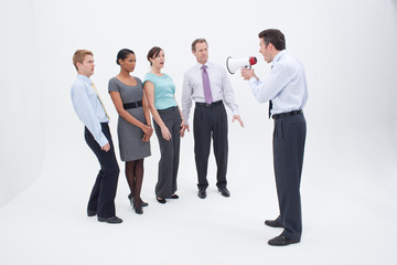 Manager shouting at businesspeople with megaphone