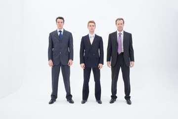 Three serious businessmen standing in row