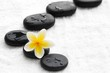 zen stones with frangipani flower on white towel