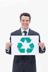 Smiling businessman holding recycling symbol