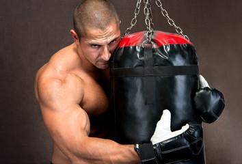 Athletic young man training kickboxing using black punching bag