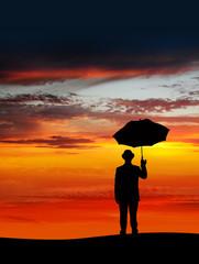 businessman holding an umbrella in sunset